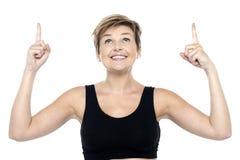 Γυναίκα που κοιτάζει και που δείχνει προς τα πάνω και με τα δύο χέρια Στοκ εικόνες με δικαίωμα ελεύθερης χρήσης
