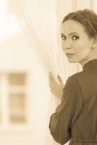 Γυναίκα που κοιτάζει μέσω της αναμονής παραθύρων Στοκ φωτογραφία με δικαίωμα ελεύθερης χρήσης