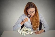 Γυναίκα που κοιτάζει μέσω της ενίσχυσης - γυαλί στο σωρό των τραπεζογραμματίων δολαρίων Στοκ φωτογραφία με δικαίωμα ελεύθερης χρήσης