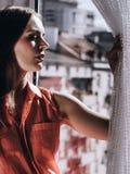 Γυναίκα που κοιτάζει μέσω του παραθύρου, χαλάρωση στοκ φωτογραφία