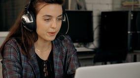 Γυναίκα που κοιτάζει στην επίδειξη lap-top και που χρησιμοποιεί την κάσκα και το μικρόφωνο απόθεμα βίντεο