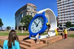 Γυναίκα που κοιτάζει τότε σε ένα γιγαντιαίο ρολόι με τα παιδιά Δημόσιο πάρκο κοντά στην παραλία Riazor Λα Κορούνια, Ισπανία, στις στοκ εικόνες