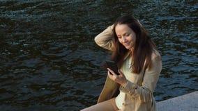 Γυναίκα που κουβεντιάζει στο smartphone, που κάθεται ενάντια στο πάρκο ποταμών φιλμ μικρού μήκους
