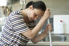 Γυναίκα που κουράζεται στήριξη στη σφουγγαρίστρα Στοκ Εικόνες