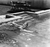 Γυναίκα που κολυμπά σε μια λίμνη με μια κολύμβηση ΚΑΠ (όλα τα πρόσωπα που απεικονίζονται δεν ζουν περισσότερο και κανένα κτήμα δε Στοκ Φωτογραφίες