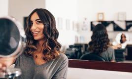 Γυναίκα που κρατά έναν μικρό στρογγυλό καθρέφτη στο σαλόνι ομορφιάς Στοκ φωτογραφίες με δικαίωμα ελεύθερης χρήσης