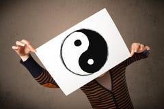 Γυναίκα που κρατά ένα έγγραφο με ένα yin-yang σε το μπροστά από το κεφάλι της Στοκ φωτογραφία με δικαίωμα ελεύθερης χρήσης
