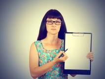 Γυναίκα που κρατά ένα κενό έγγραφο δείχνοντας πού να τεθεί η υπογραφή Στοκ Εικόνες