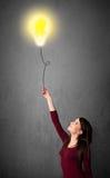 Γυναίκα που κρατά ένα μπαλόνι lightbulb Στοκ Φωτογραφίες