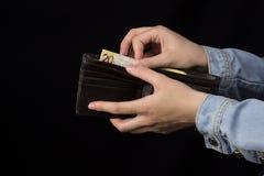 Γυναίκα που κρατά ένα πορτοφόλι με τα χρήματα, κινηματογράφηση σε πρώτο πλάνο, μαύρο υπόβαθρο, τραπεζογραμμάτιο, ευρο- στοκ φωτογραφία