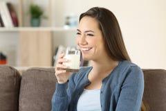 Γυναίκα που κρατά ένα ποτήρι του γάλακτος σε έναν καναπέ στοκ εικόνες με δικαίωμα ελεύθερης χρήσης