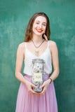 Γυναίκα που κρατά ένα σύνολο μπουκαλιών της αποταμίευσης χρημάτων Στοκ Φωτογραφία