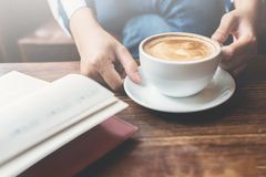 Γυναίκα που κρατά ένα φλιτζάνι του καφέ με το ανοικτό σημειωματάριο στο πρώτο πλάνο ο Στοκ Φωτογραφίες