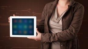 Γυναίκα που κρατά μια άσπρη ταμπλέτα με τα μουτζουρωμένα apps Στοκ Εικόνες