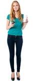 Γυναίκα που κρατά μια κούπα του καφέ και ενός κινητού Στοκ εικόνα με δικαίωμα ελεύθερης χρήσης
