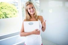 Γυναίκα που κρατά μια κλίμακα στάθμισης με τους αντίχειρες επάνω Στοκ φωτογραφία με δικαίωμα ελεύθερης χρήσης