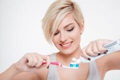 Γυναίκα που κρατά μια οδοντόβουρτσα και που τοποθετεί την οδοντόπαστα Στοκ φωτογραφία με δικαίωμα ελεύθερης χρήσης