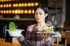 Γυναίκα που κρατά μια σαλάτα και burger Γυναίκα που επιλέγει μεταξύ της υγιούς και ανθυγειινής κατανάλωσης Στοκ εικόνες με δικαίωμα ελεύθερης χρήσης