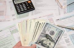 Γυναίκα που κρατά τα αμερικανικά δολάρια στο υπόβαθρο των φορολογικών μορφών στοκ εικόνες