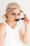 Γυναίκα που κρατά τα διαθέσιμα μαύρα γυαλιά ηλίου Στοκ Εικόνες