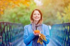 Γυναίκα που κρατά τα κίτρινες φύλλα και την κολοκύθα δέντρων σφενδάμνου στο πάρκο autum Στοκ φωτογραφίες με δικαίωμα ελεύθερης χρήσης
