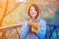 Γυναίκα που κρατά τα κίτρινες φύλλα και την κολοκύθα δέντρων σφενδάμνου στο πάρκο autum Στοκ Φωτογραφίες