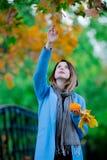 Γυναίκα που κρατά τα κίτρινες φύλλα και την κολοκύθα δέντρων σφενδάμνου στο πάρκο autum Στοκ Φωτογραφία