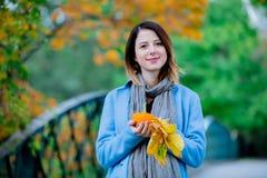 Γυναίκα που κρατά τα κίτρινες φύλλα και την κολοκύθα δέντρων σφενδάμνου στο πάρκο autum Στοκ Εικόνες