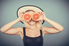Γυναίκα που κρατά τα κόκκινα φρούτα γκρέιπφρουτ όπως eyeglasses Στοκ εικόνα με δικαίωμα ελεύθερης χρήσης