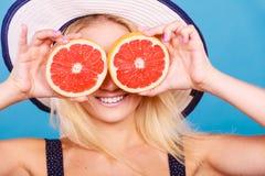 Γυναίκα που κρατά τα κόκκινα φρούτα γκρέιπφρουτ όπως eyeglasses Στοκ φωτογραφίες με δικαίωμα ελεύθερης χρήσης
