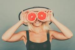 Γυναίκα που κρατά τα κόκκινα φρούτα γκρέιπφρουτ όπως eyeglasses Στοκ εικόνες με δικαίωμα ελεύθερης χρήσης