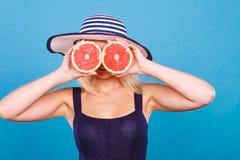 Γυναίκα που κρατά τα κόκκινα φρούτα γκρέιπφρουτ όπως eyeglasses Στοκ φωτογραφία με δικαίωμα ελεύθερης χρήσης