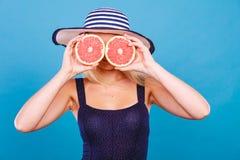 Γυναίκα που κρατά τα κόκκινα φρούτα γκρέιπφρουτ όπως eyeglasses Στοκ Φωτογραφίες