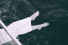 Γυναίκα που κρατά τα πόδια της επάνω από τη θάλασσα Στοκ εικόνες με δικαίωμα ελεύθερης χρήσης