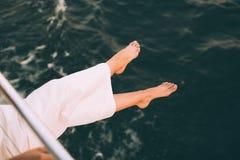 Γυναίκα που κρατά τα πόδια της επάνω από τη θάλασσα Στοκ Εικόνες
