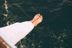 Γυναίκα που κρατά τα πόδια της επάνω από τη θάλασσα Στοκ Εικόνα