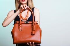 Γυναίκα που κρατά την καφετιά τσάντα δέρματος Στοκ εικόνα με δικαίωμα ελεύθερης χρήσης
