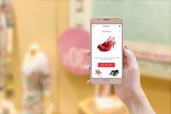 Γυναίκα που κρατά το έξυπνο τηλέφωνο με το σε απευθείας σύνδεση κατάστημα app στην οθόνη κατά την μπροστινή άποψη Στοκ φωτογραφία με δικαίωμα ελεύθερης χρήσης