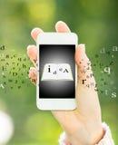 Γυναίκα που κρατά το έξυπνο τηλέφωνο με το ebook Στοκ εικόνα με δικαίωμα ελεύθερης χρήσης