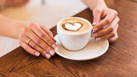 Γυναίκα που κρατά το καυτό φλιτζάνι του καφέ, με τη μορφή καρδιών στοκ εικόνες με δικαίωμα ελεύθερης χρήσης