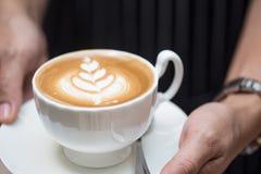 Γυναίκα που κρατά το καυτό φλιτζάνι του καφέ στοκ φωτογραφία