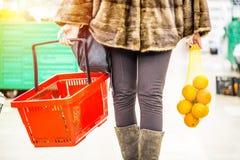 Γυναίκα που κρατά το κόκκινα καλάθι και τα πορτοκάλια αγορών στο κατάστημα υπεραγορών ψωνίζοντας λευκή γυναίκα ποδιών έννοιας τσα Στοκ Φωτογραφία
