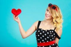 Γυναίκα που κρατά το κόκκινο σύμβολο αγάπης καρδιών Στοκ Εικόνες