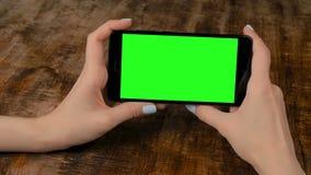 Γυναίκα που κρατά το μαύρο smartphone με την κενή πράσινη οθόνη - βασική έννοια χρώματος απόθεμα βίντεο