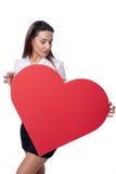 Γυναίκα που κρατά το μεγάλο κόκκινο έμβλημα μορφής καρδιών Στοκ Φωτογραφία