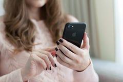 Γυναίκα που κρατά το νέο iPhone 7 αεριωθούμενο μαύρο Onyx Στοκ Εικόνες