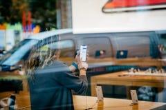 Γυναίκα που κρατά το πιό πρόσφατο iPhone Χ η εσωτερική Apple Store Στοκ εικόνα με δικαίωμα ελεύθερης χρήσης