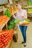 Γυναίκα που κρατά ψηλά υπερήφανα τα λαχανικά καλαθιών Στοκ εικόνα με δικαίωμα ελεύθερης χρήσης