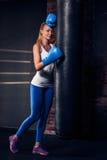 Γυναίκα που κλίνει ενάντια σε μια τσάντα διατρήσεων στα μπλε εγκιβωτίζοντας γάντια Στοκ Εικόνες