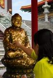 Γυναίκα που κλείνει το χρυσό φύλλο στο Βούδα στοκ φωτογραφίες